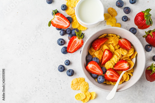 Tela Cornflakes with strawberries and blueberries in a bowl on white background, top view