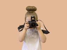 A Little Girl In Business Clothes Holds A Reflex Camera In Her Hands In Front Of Her Face. The Child Wants To Take A Picture. The Baby Holds Her Finger On The Shutter Button.