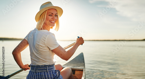 фотографія  Smiling young woman canoeing on a lake in summer