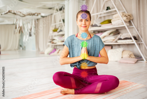 Fototapety, obrazy: mindfulness, spirituality and healthy lifestyle concept - woman meditating in lotus pose at yoga studio with seven chakra symbols