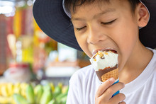 Asian Boys Wearing A Hat Eating Ice Cream Cone In Hand.
