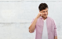 Idea, Intelligence And Imagination Concept - Smiling Young Man Pointing Finger To His Temple Over Grey Concrete Wall Background