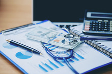Financial Analysis, Audit Or Accounting - Stethoscope Over A Calculator And Dollar Bills. Medical Costs, Financial Concept