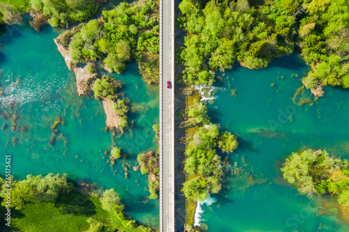 Poster Rivière de la forêt Red car crossing road bridge over Mreznica river in Croatia, overhead shot of countryside landscape, waterfalls and trees in spring