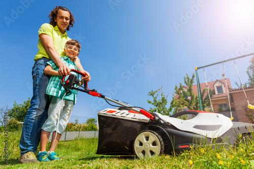 Fototapeta Father teaching son edging the lawn with lawnmower obraz
