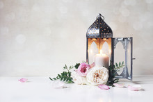 Festive Greeting Card, Invitation For Muslim Holiday Ramadan Kareem.Vintage Moroccan Lantern With Glowing Candle, Green Branches, Pink Roses Flowers And Floral Petals On Table. Glittering Bokeh Lights