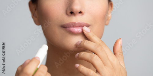 Fotografia Lips skin care. Afro woman applying balsam