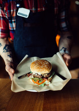Waiter Holding Big Fresh Burger With Beef Cutlet And Vegetables