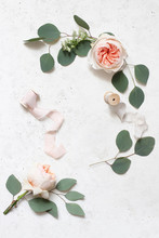 Feminine Wedding, Birthday Still Life Scene. Silk Ribbons, Eucalyptus Leaves And Blush Pink English Roses Flowers. Concrete Table Background. Flat Lay, Top View,vertical. Empty Copy Space.