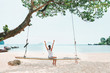 Young woman on swings on white sea beach