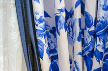 Curtains With Blue Floral Pattern And White Tulle On The Windows Of The Living Room.