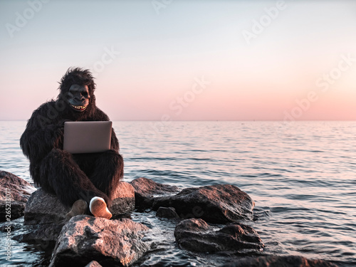Obraz na plátně A man in a monkey costume at sunset near the sea works on a computer against the backdrop of a modern skyscraper