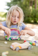 Little Girl With Blonde Hair Doing Arts And Crafts Outdoors