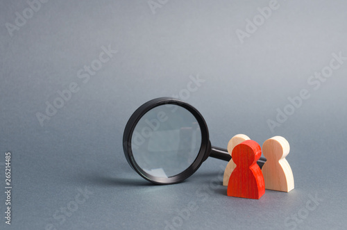 Three wooden human figure stands near a magnifying glass on a gray background Canvas Print