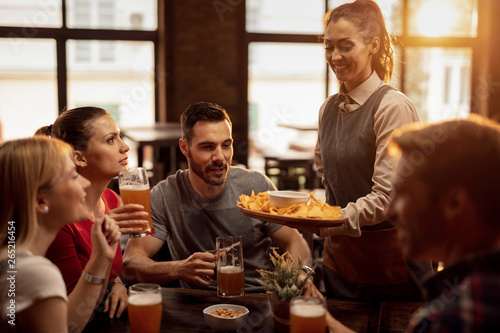 Fotografía  Happy waitress serving nacho chips to group of friend in a pub.