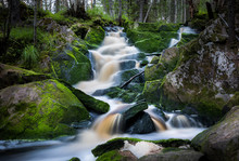 Waterfall Flowing Over Mossy Rocks In Forest