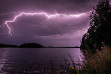 Purple Lightning Streak Through Clouds Over Water
