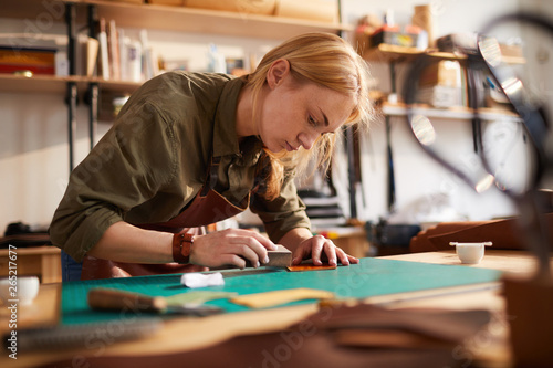 Warm toned portrait of female artisan  tracing leather patterns while working in Wallpaper Mural