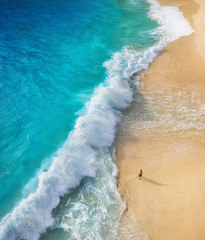 Panel Szklany Optyczne powiększenie View of a man on the beach on Bali, Indonesia. Vacation and adventure. Top view from drone at beach, azure sea and relax man. Travel and relax - image