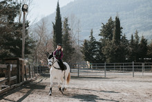 Sweet Little Girl In Helmet Riding Obedient White Horse In Enclosure During Lesson On Autumn Day On Ranch