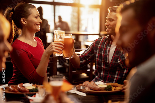 Happy couple toasting with beer while having lunch with friends in a restaurant.