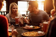 Young couple drinking beer and eating lunch with friends in a pub.