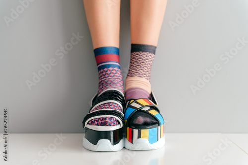Beautiful female legs in mismatched trendy socks standing in two different fashionable high wedge leather sandals on white surface Fototapete