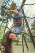 Cute girl having fan on playground Charming little brunette girl in jeans suit hanging upside down on grid and looking at camera on playground in park