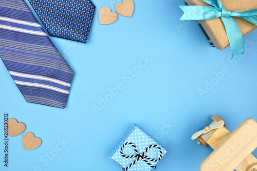 Fathers Day frame of gifts, ties and hearts on a blue background. Top view with copy space,