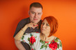 Couple of lovers on an orange background. The husband and wife, the concept of family. Young man and woman with bright red hair