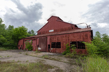 Large Red Abandoned Building With Cloudy Sky And Overgrown Brush