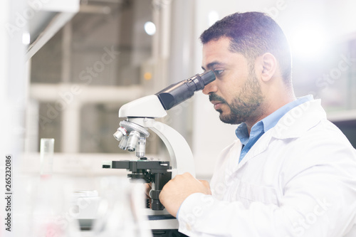 Photo  Serious focused handsome young Arabian biologist sitting at desk and using micro