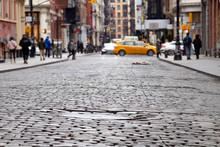 Cobblestone Street View Of The Busy Intersection Of Broome And Greene Streets With People And Taxi In The SoHo Neighborhood Of Manhattan In New York City