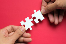 Partnership Concept With Hands Putting Puzzle Pieces Together On Red Background