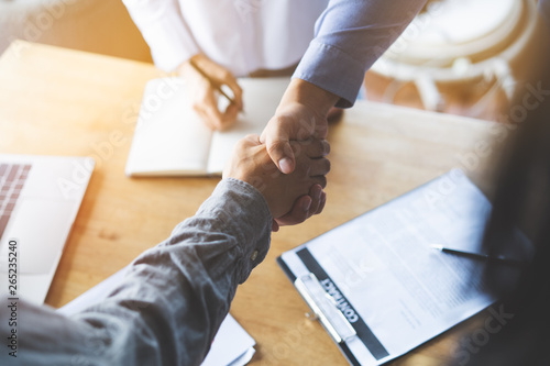 Photo  Two businessmen handshaking in meeting after final project agreement deal done