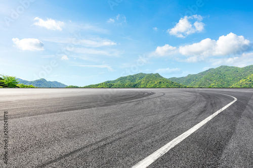 Photo sur Aluminium F1 Asphalt race track ground and green mountains natural landscape