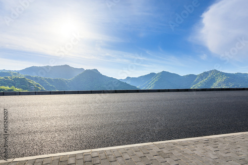 Country highway and green mountains natural landscape under the blue sky