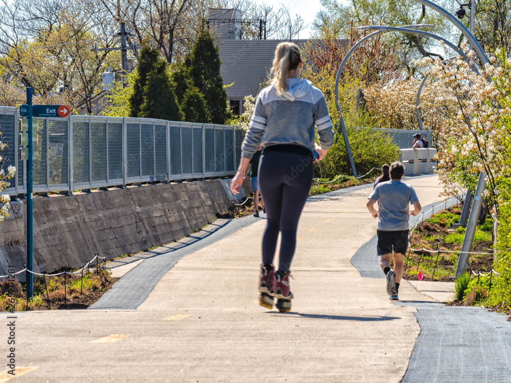 Fototapety, obrazy: A woman is rollerblading riding skates and a man is jogging on The 606 Bloomingdale Train in Humboldt Park. Streets of Chicago, main streets in Illinois.