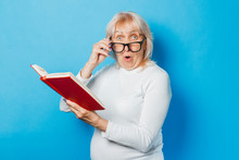 An Old Woman In Glasses With A Surprised Face Is Reading A Book On A Blue Background. Concept Old Lady Reads Books, Education, Book Club.