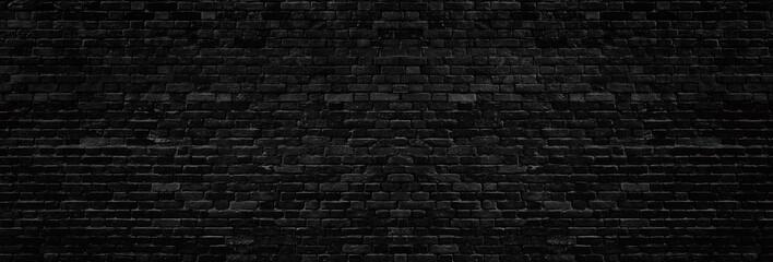 Široka stara crna otrcana tekstura zida od opeke. Tamna zidana panorama. Cigla panoramska grunge pozadina