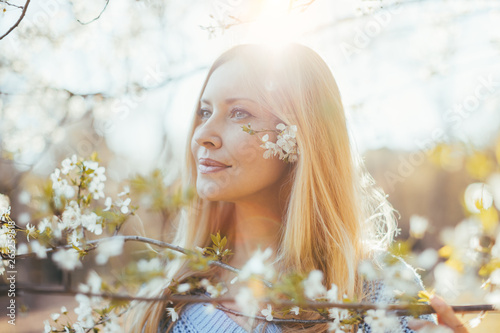 Fotografiet  Beautiful blond hair middle aged woman posing with blooming jasmine tree