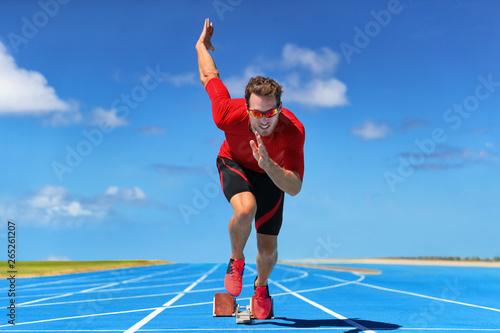 Fotografía Runner athlete starting running at start of run track on blue running tracks at outdoor athletics and fiel stadium