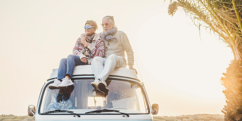 Wanderlust and travel destination happiness concept with old senior beautiful couple sitting and enjoying the outdoor freedom on the roof of vintage van vehicle together - sun backlight