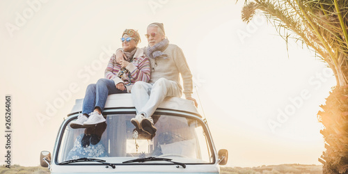 Fototapety, obrazy: Wanderlust and travel destination happiness concept with old senior beautiful couple sitting and enjoying the outdoor freedom on the roof of vintage van vehicle together - sun backlight