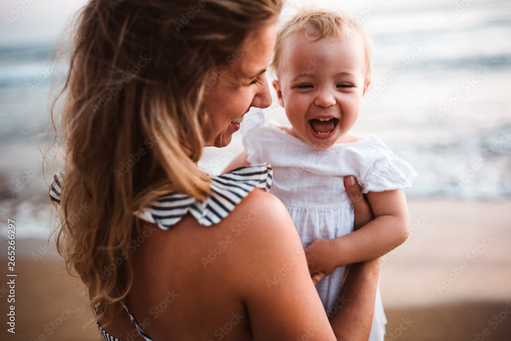 Fototapety, obrazy: Close-up of young mother with a toddler girl on beach on summer holiday.