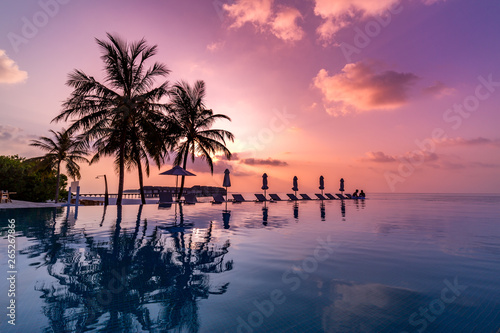 Obraz na plátně  Sunrise blue and pink light scattering across the clouds and pool, reflecting the infinity pool and silhouetted palm trees
