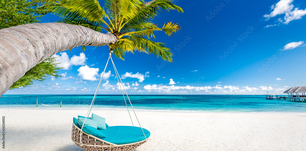 Fototapeta Tropical beach background as summer landscape with beach swing or hammock and white sand and calm sea for beach banner. Perfect beach scene vacation and summer holiday concept. Boost up color process