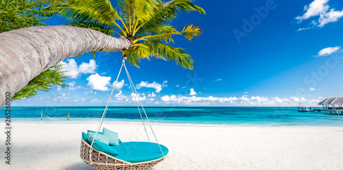 Tropical beach background as summer landscape with beach swing or hammock and white sand and calm sea for beach banner. Perfect beach scene vacation and summer holiday concept. Boost up color process