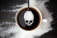 Unhealthy White Sugar Concept. Scull Spoon With Sugar And Cup Of Black Coffee On Wooden Background