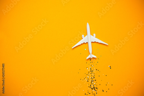 Foto  Toy airplane with sparkles on yellow background. Journey